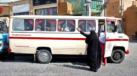 yazd : YAZD, IRAN - OCTOBER 18, 2017:  Pupils in orange islamic uniform enter their school bus after excursion to Jame Mosque in old town, on October 18 in Yazd.