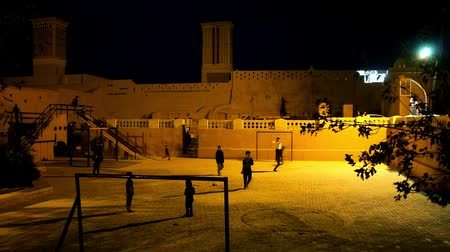 yazd : YAZD, IRAN - OCTOBER 18, 2017: Kids play football on the playground, located among the medieval buildings of the old town, the wind tower is seen on background, on October 18 in Yazd.