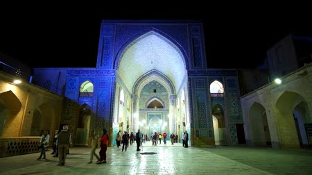 yazd : YAZD, IRAN - OCTOBER 18, 2017: Tourists leave the Jameh mosque after visiting this beautiful museum complex, the central portal decorated with evening lights, on October 18 in Yazd. Stock Footage