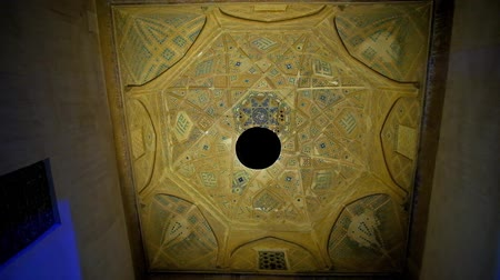 yazd : The dome of entrance portal of Jameh mosque - the old metal lamp is swaying in the wind and changing the lighting of decorated ceiling, Yazd, Iran. Stock Footage