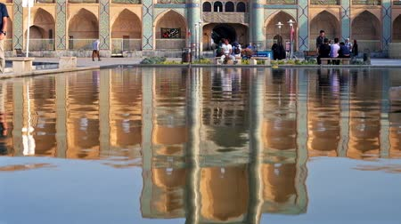 caravanserai : YAZD, IRAN - OCTOBER 18, 2017: The fountain in Amir Chakhmaq square reflects scenic architectural complex, the most popular city location with stores and cafes, on October 18 in Yazd.