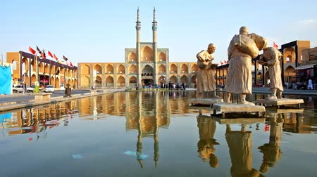 caravanserai : YAZD, IRAN - OCTOBER 18, 2017: Relax at the fountain with water carriers, located in the central square of Amir Chakhmaq, on October 18 in Yazd.