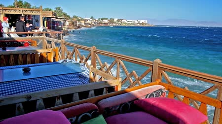 aqaba : DAHAB, EGYPT - DECEMBER 25, 2017: The summer terraces of coastal cafes are empty during the strong waves and windy weather in Aqaba gulf, on December 25 in Dahab.