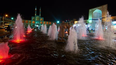 yazd : YAZD, IRAN - OCTOBER 18, 2017: Fountain light show in Amir Chakhmaq square, the water carriers sculpture is seen between the fountains and Hosseinieh located in the distance, on October 18 in Yazd.