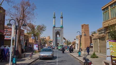 yazd : YAZD, IRAN - OCTOBER 18, 2017: The walk along the market stores and cafes of Masjid Jame street to the Jame Mosque (Friday Mosque) with blue tiled portal and tall minarets, on October 18 in Yazd.