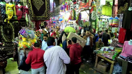 khalili : CAIRO, EGYPT - DECEMBER 20, 2017: The crowded narrow walkway along Jawhar Al Qaed street of Khan El Khalili bazaar with bright stalls, full of different goods, on December 20 in Cairo.
