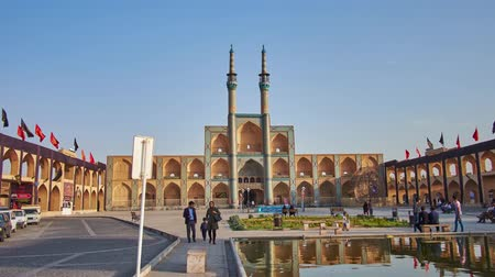 caravanserai : YAZD, IRAN - OCTOBER 18, 2017: The walk along Amir Chakhmaq square to the building of Hosseinieh with multiple arched niches and tall minarets, decorated with tiled patterns, on October 18 in Yazd. Stock Footage
