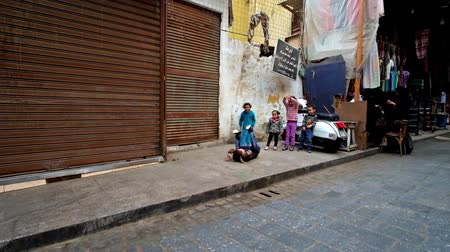 khalili : CAIRO, EGYPT - DECEMBER 20, 2017: The little children play in El Gamaleya street of Khan El Khalili, the laughing  boy perform a somersault, on December 20 in Cairo.