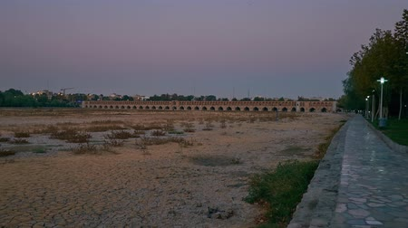 ispahan : ISFAHAN, IRAN - OCTOBER 21, 2017: The evening walk in City Park along the bank of dried-out Zayandeh river with a view on Siosepol (Allahverdi Khan) arched bridge, on October 21 in Isfahan.