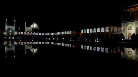 ispahan : The night panorama of Naqsh-e Jahan square with its landmarks - the Qapu palace, Imam Mosque, Sheikh Lotfollah Mosque and arcades of Grand Bazaar are reflected in black waters of pond, Isfahan, Iran. Stock Footage