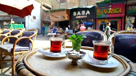 khalili : CAIRO, EGYPT - DECEMBER 21, 2017: Two glasses of hot black tea with fresh mint in outdoor cafe of Al Muizz street, Khan El Khalili Bazaar, on December 21 in Cairo.
