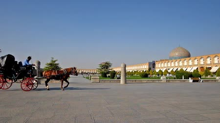 ispahan : ISFAHAN, IRAN - OCTOBER 20, 2017: The scenic Naqsh-e Jahan Square with long arcades of Grand Bazaar, dome of Sheikh Lotfollah mosque, beautiful garden and riding carriage, on October 20 in Isfahan