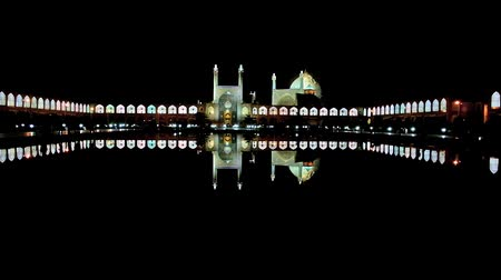 ispahan : The clear night reflection of illuminated Royal Mosque and pavilions of Grand Bazaar in black waters of pond in the middle of Naqsh-e Jahan square of Isfahan, Iran. Stock Footage