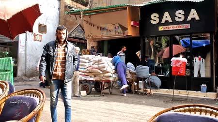 khalili : CAIRO, EGYPT - DECEMBER 21, 2017: The porter unloads bags with goods from the large cart in Al Muizz street of Khan El Khalili Bazaar, Islamic Cairo district, on December 21 in Cairo. Stock Footage
