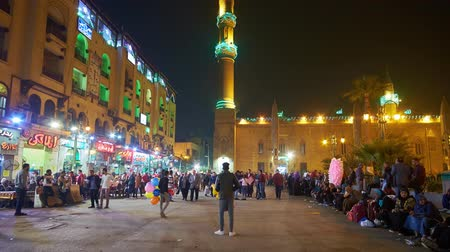 khalili : CAIRO, EGYPT - DECEMBER 22, 2017: Hasan El-Adawy Square is busy part of  Khan El Khalili Bazaar in Islamic Cairo, the mosque of Al-Hussain is the main landmark of this location, on December 22 Cairo Stock Footage