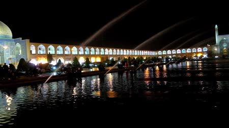 ispahan : The scenic panoramic view of evening Nagsh-e Jahan square with refreshing fountains and brightly illuminated medieval mosques, palaces and arcades of Grand Bazaar, Isfahan, Iran.