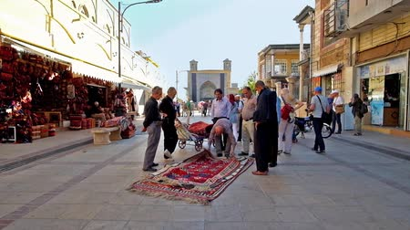 porters : SHIRAZ, IRAN - OCTOBER 14, 2017: The busy street of Vakil Bazaar, the porters, providers and rug merchants check the quality of large carpets, on October 14 in Shiraz.