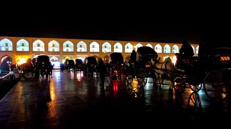 ispahan : ISFAHAN, IRAN - OCTOBER 20, 2017: Evening ride in horse carriage along medieval Nagsh-e Jahan Square is one of the most romantic attractions in old town, on October 20 in Isfahan.