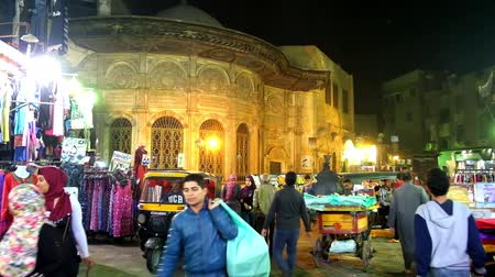 khalili : CAIRO, EGYPT - DECEMBER 21, 2017: The evening shopping in Al Muizz street of Khan El Khalili Bazaar, the medieval sabil-kuttab of Tusun Pasha is seen behind the stalls, on December 21 in Cairo.