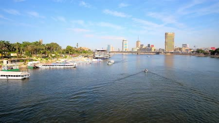 nil : CAIRO, EGYPT - DECEMBER 24, 2017: Qasr El Nil bridge overlooks the bank of Gezira Island with tourist harbor, full of pleasure boats and the bank of Downtown district, on December 24 in Cairo