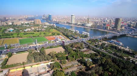 nil : CAIRO, EGYPT - DECEMBER 24, 2017: Aerial view of Gezira Island with wide green areas - gardens or park and Downtown district with dense housing, on December 24 in Cairo Stok Video