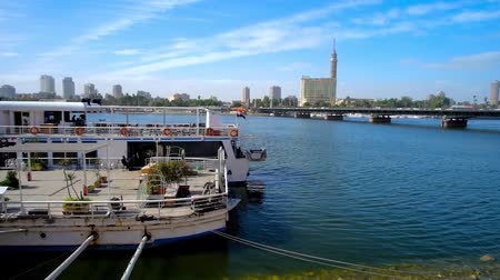 nil : CAIRO, EGYPT - DECEMBER 24, 2017: The ship restaurant at the Nile bank with a view on Qasr El Nil bridge and Gesira Island with tall and slender Cairo Tower, on December 24 in Cairo