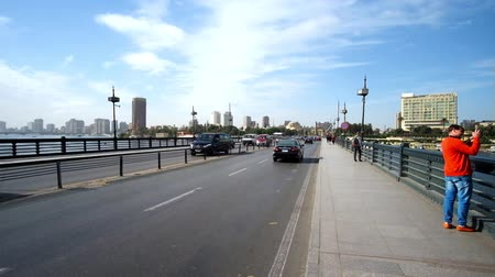 nil : CAIRO, EGYPT - DECEMBER 24, 2017: The walk along the Qasr El Nil bridge with the view on Cairo Tower and fast traffic, on December 24 in Cairo Stok Video