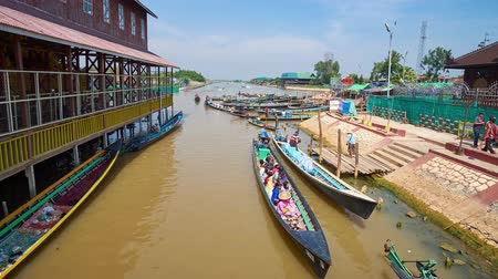 nyaung u : INLE, MYANMAR - FEBRUARY 18, 2018: The canoe boats with tourists and Buddhist pilgrims at the wharf of Hpaung Daw U Pagoda, located on Inle lake, on February 18 in Inle. Stock Footage
