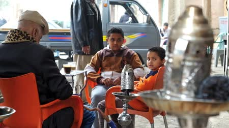 khalili : CAIRO, EGYPT - DECEMBER 22, 2017: The smoking hookah grandfather with his little grandsons in outdoor tea and shisha cafe, located in Abdel-Maguid El-Labban street, on December 22 in Cairo, Egypt. Stock Footage