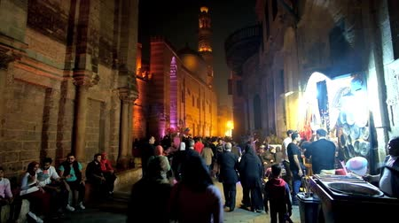 khalili : CAIRO, EGYPT - DECEMBER 22, 2017: Evening Al-Muizz street is the popular walkway with multiple market stalls, offering cotton candy, nuts, sweet potato and other snacks, on December 22 in Cairo.