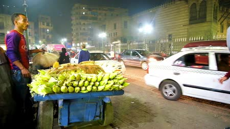 khalili : CAIRO, EGYPT - DECEMBER 22, 2017: The street vendor sells the fresh corn from the old cart on the road in Al Azhar avenue with heavy evening traffic, on December 22 in Cairo. Stock Footage