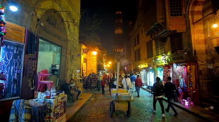 khalili : CAIRO, EGYPT - DECEMBER 22, 2017: The street vendor with his cart offers the snacks in crowded Al-Muizz street, popular place for the evening walks, on December 22 in Cairo.
