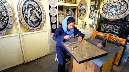 ispahan : ISFAHAN, IRAN - OCTOBER 21, 2017: The interesting workshop in Grand Bazaar - craftswoman demonstrates the Persian art of Ghalam Zani, the carving design on metal, on October 21 in Isfahan.