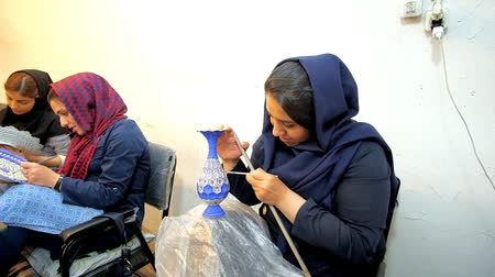 ispahan : ISFAHAN, IRAN - OCTOBER 21, 2017: The young artisan create a pattern on engraved vase in traditional old meenakari enamel technique, on October 21 in Isfahan.