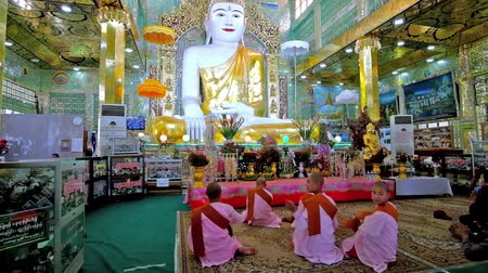 soon : SAGAING, MYANMAR - FEBRUARY 21, 2018: Image house of Soon Oo Pon Nya Shin Pagoda, bhikkhunis (Buddhist nuns) are praying at the altar with giant golden statue of Buddha, on February 21 in Sagaing.
