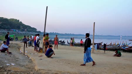 u boats : MANDALAY, MYANMAR - FEBRUARY 21, 2018: Teenagers play national Burmese game - chinlone (caneball) in evening time at the harbor on Taungthaman Lake with local onlookers, on February 21 in Mandalay.