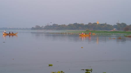 u boats : The foggy evening on Taungthaman Lake, green bank of Amarapura is seen on background, traditional wooden boats sailing to the U Bein bridge to watch the sunset, Mandalay, Myanmar. Stock Footage
