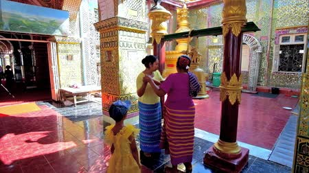 mianmar : MANDALAY, MYANMAR - FEBRUARY 23, 2018: Two women ring the large bell with wooden block in prayer hall of Su Taung Pyae Pagoda, performing the Buddhist ritual, on February 23 in Mandalay.