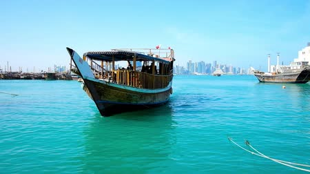 islámský : DOHA, QATAR - FEBRUARY 13, 2018: The wooden pleasure boat sails to the harbor of Doha with a view on modern skyscrapers on background, on February 13 in Doha.