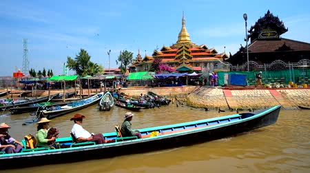 u boats : INLE LAKE, MYANMAR - FEBRUARY 18, 2018: The Hpaung Daw U Pagoda, located on canal of Inle Lake and surrounded by wharf with tourist canoes, Ywama village, on February 18 in Inle lake.