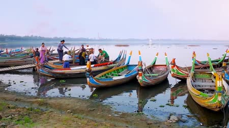 u boats : MANDALAY, MYANMAR - FEBRUARY 21, 2018: The small harbor on Taungthaman Lake with numerous colored boats, offering sunset trips to U Bein Bridge, on February 21 in Mandalay.
