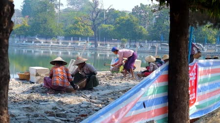 mianmar : MANDALAY, MYANMAR - FEBRUARY 21, 2018: Burmese people during manual construction works on embankment of the Citadels moat, on February 21 in Mandalay.