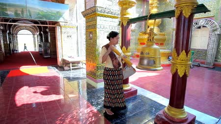 suéter : MANDALAY, MYANMAR - FEBRUARY 23, 2018: The bell ringing is important ritual in Buddhism, the Burmese worshiper performs it in Su Taung Pyae Pagoda, on February 23 in Mandalay.