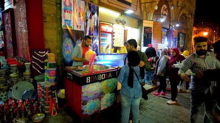 khalili : CAIRO, EGYPT - DECEMBER 22, 2017: Young Egyptian couple wait for cotton candy, being made by the street sweets vendor in evening Khan El Khalili market, Al-Muizz street, on December 22 in Cairo.