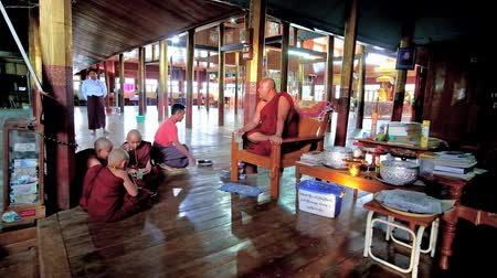 mianmar : INLE LAKE, MYANMAR - FEBRUARY 18, 2018: Bhikkhu (Buddhist monk) drinks lemonade with samaneras (novice monks) in prayer hall of Nga Phe Kyaung Monastery of jumping cats, on February 18 in Inle lake. Stock Footage