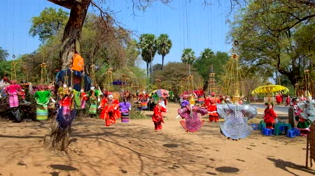 pagan kingdom : Traditional handmade string puppets in colored dresses and bright sunshades hang on the tree and flutter on the wind in archaeological site of old Bagan, Myanmar. Stock Footage
