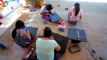 lacquerware : BAGAN, MYANMAR - FEBRUARY 24, 2018: Visit lacquerware workshop and watch the craftsmanship - young artisans create the images on lacquered surface, using etching needles, on February 24 in Bagan.