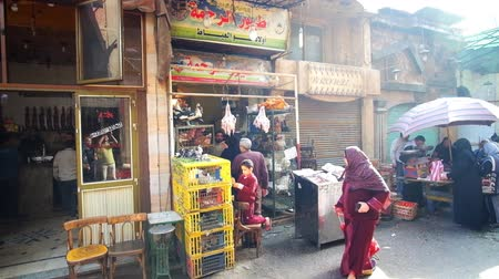 khalili : CAIRO, EGYPT - DECEMBER 21, 2017: The shabby food stores of Khan El Khalili bazaar, stretching along the narrow busy street of old neighborhood, on December 21 in Cairo.