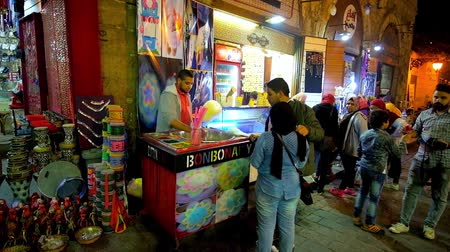 khalili : CAIRO, EGYPT - DECEMBER 22, 2017: The street vendor makes the cotton candy for the young Egyptians, spending their time in evening Al-Muizz street in historical district, on December 22 in Cairo.