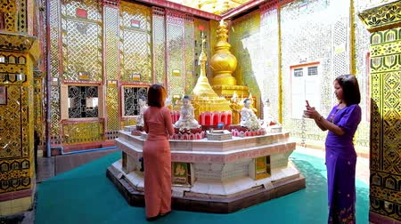 suéter : MANDALAY, MYANMAR - FEBRUARY 23, 2018: The young Burmese worshiper decorates the statue of Lord Buddha with fragrant flower garlands in Su Taung Pyae Pagoda, on February 23 in Mandalay. Stock Footage